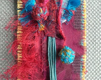 Textile pin/medal. Red, purple and blue deep. Baroque spirit.