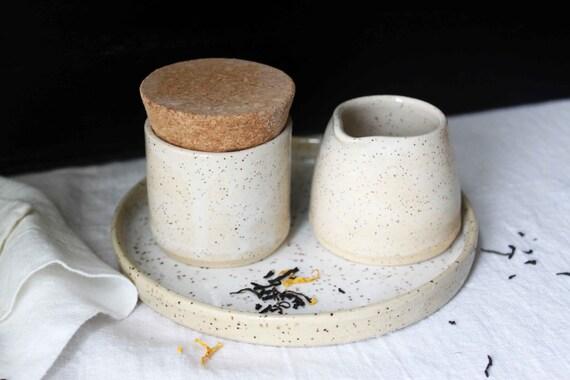 La main blanche carreaux ensemble la crème et le sucre en céramique de grès.