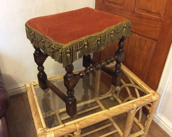 Vintage wooden upholstered stool on castors