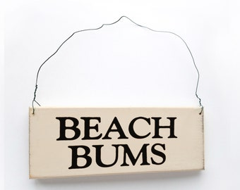 """Wood Sign Saying """"Beach Bums"""" White Wood With Black Lettering."""