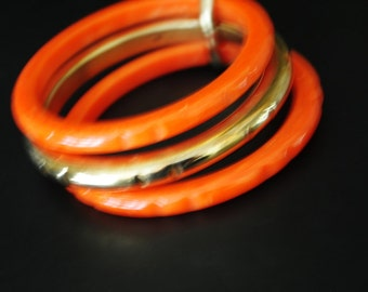 Mod vintage 50s  tangerine bakelite , carved , three ring bracelet with a gold tone metal centerpiece.One size fits all.