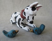 Miniature handbuilt clay dog sculpture of spotted Great Dane with bluebirds