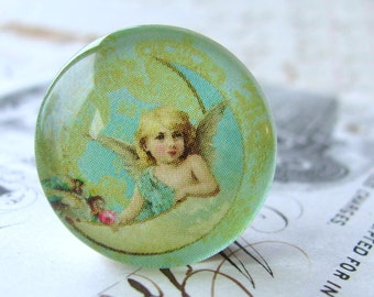 Cherub on the moon, angel image, mint green, aqua blue, yellow, handmade glass cabochon, round 22mm cabochon, flat back image