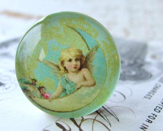 Cherub on the moon, angel image, mint green, aqua blue, yellow, handmade glass cabochon, round 22mm cabochon, flat back image