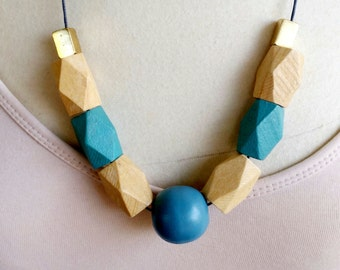 Wooden bead necklace. Features geometric beads. wood and metal. pastel. natural. teal. blue.