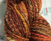 Hand spun merino yarn. 'Bonfire' blend of orange, yellow, rusty brown and a hint of copper sparkle. 135gms DK weight.