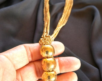 Gold tone multi-chain three bead tassel necklace