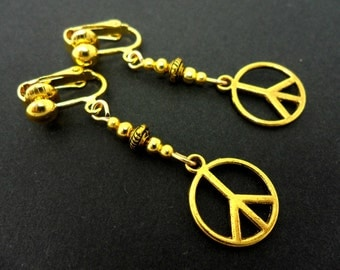 A pair of cute little gold tone  peace sign dangly clip on earrings.