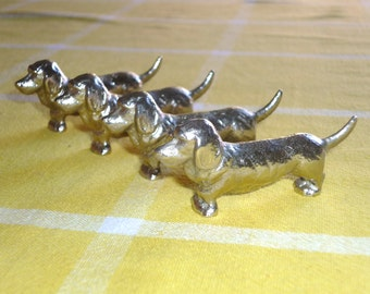 Four French dog cutlery/knife rests