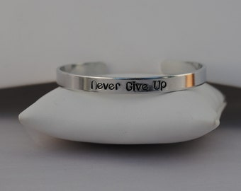 Never Give Up 1/4 in Hand Stamped Aluminum Cuff