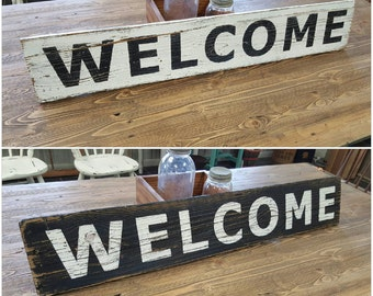 Large distressed hand painted horizontal WELCOME sign on reclaimed wood.