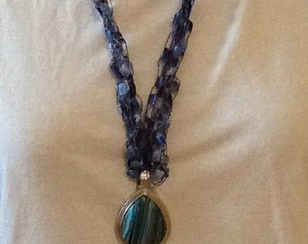 Knitted Ribbon Necklace with blue pendant.