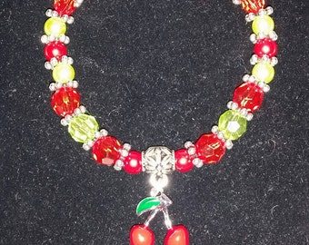 Red and pale green beaded bracelet with cherries charm.