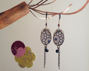 Bronze earrings and Japanese paper flowers gold on a blue background.