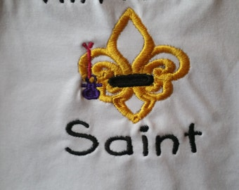 I'm a Lil Saint in Black Embroidery Thread on aWhite Baby Bib With Pacifier on a String Hanging From A Gold Fleur De Lis
