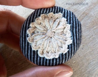 Textile brooch white flower on striped background.