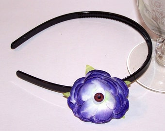 purple and white eyeball flower on black hair band