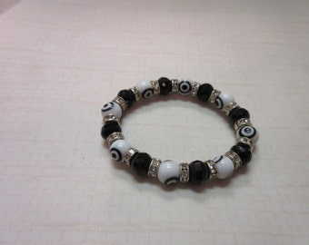 White evil eye beaded bracelet with solid black beads.