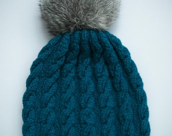 Turquoise knit hat with rabbit pom pom