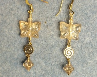 Tan gold Czech glass butterfly bead dangle earrings adorned with gold swirly connectors and tan gold Saturn beads.