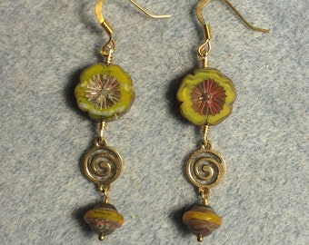 Yellow green Czech glass pansy bead dangle earrings adorned with gold swirly connectors and yellow green Czech glass Saturn beads.