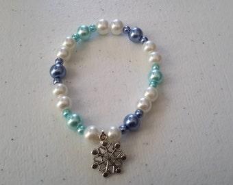 Adult/teen size stretch bracelet. Winter themed. Blue, white, aqua, pearls. Snowflake charm.