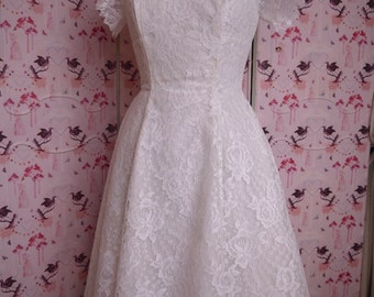 Knee length  50's / 60's vintage lace wedding dress. Simple, sweet and  pretty, approx size 8. Fairly short skirt and lovely fitted shape.
