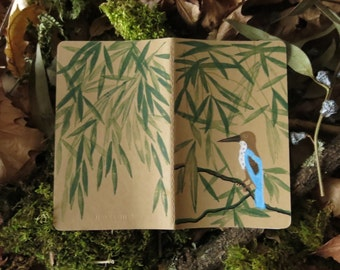 Notebook moleskine with a hand illustrated bird hidden into the bamboo leaves