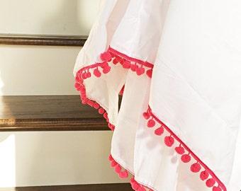 White and pink pom pom crib skirt