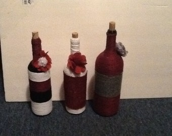 Three seperate wine bottles, wrapped in yarn