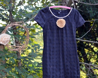 short sleeve black tunic length blouse with polka dot print and hand made flower