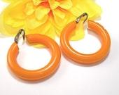 """Bakelite Hoop Earrings, 1-1/4"""" Wide Clip On, Light Pumpkin Orange, Slightly Carved, Vintage c1940s"""