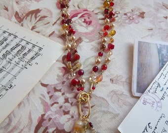 Versatile crimson and gold beaded necklace made with crystals, glass, and pearl beads