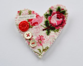 BROOCH Textile heart shaped.  Appliquéd rose trim. Hand stitched. Perfect day