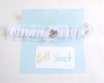 Handmade white ribbon wedding garter with silver shamrock charm