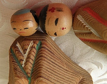 2 carved kokeshi dolls