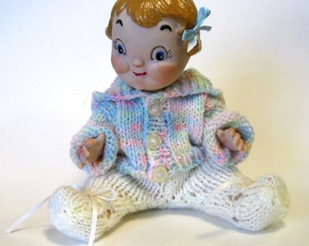 "porcelain handrafted  7"" soup can baby girl dressed in crocheted  hooded sweater and leggings"