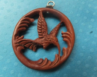 Humming bird hand carved out of wood with a loop on top for all your jewelry making needs