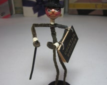 1920's-30's art deco pipe cleaner figurine doll hand painted wood face man in wood and felt top hat holds a celluloid cocktail recipe book
