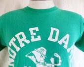 go und fightin' irish vintage 80's Notre Dame University kelly green graphic t-shirt white curve spellout logo mascot print unisex crew neck