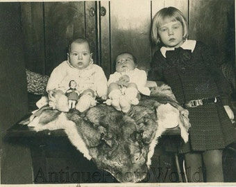Babies with toy doll on wolf hide antique photo
