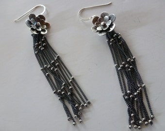 Daisy Chain Earrings swing and sway; tiny silver beads sparkling bright on dark silver tassels pouring from layered silver blooms.