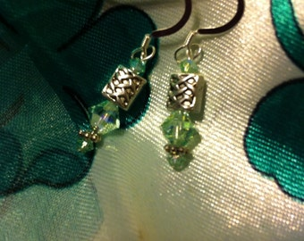 Chrysolite and silver pierced earrings with Celtic knot beads.