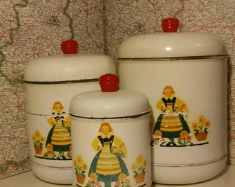 Set of three metal Nesco canisters with bright,  colorful Dutch girl printed on front.