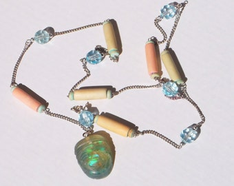 """Authentic Ford Fairlane movie artifact tiki necklace made from """"It's a Mad, Mad, Mad, Mad World"""" car glass."""
