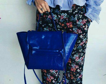 Electric blue leather bag by hand and shoulder strap