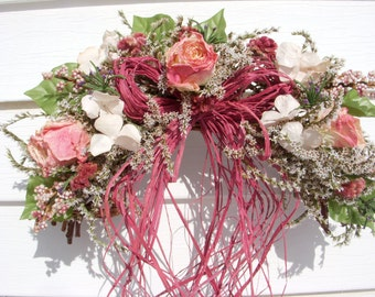 Victorian swag with a raffia bow on vine with dried roses and dried and silk flowers