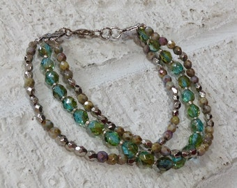 3 strand bracelet of glass and metal faceted beads.  Varying shades of green/blue/brown with silver.  Sundance inspired