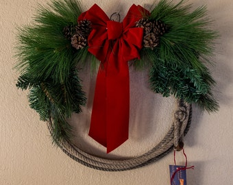 Rope wreath with red bow and pine cones