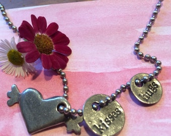 Hugs and kisses with heart with wings necklace.
